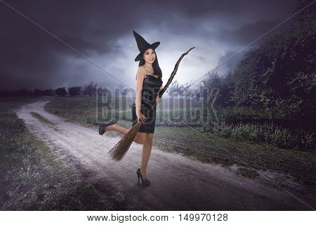 Happy Young Asian Witch With A Broom Getting Ready To Fly