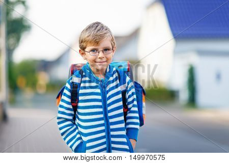 Happy little kid boy with glasses and backpack or satchel on the way to school or nursery. Child outdoors on warm sunny day, Back to school, education concept