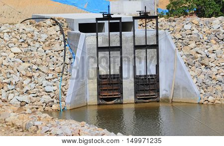 two metal sluice gates in concrete outlet for a newly dug pond, near Songkhla, Thailand