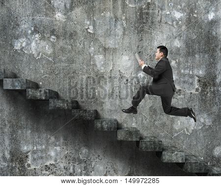 Man Using Tablet Running On Old Dirty Concrete Stairs