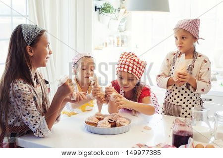 Group of children cooking in the white kitchen. Kids wearing colorful aprons baking dessert at home.