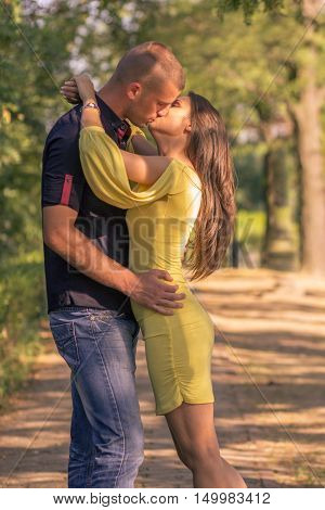 Young Adult Couple Kissing Outdoors Sunny Day