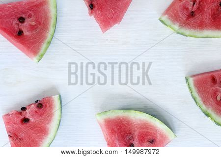 flat layout of sliced lobules of watermelon lying on the surface of the top view light / dessert frame
