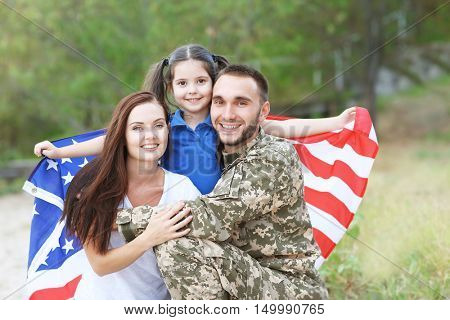 US army soldier with family and USA flag in park