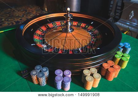A Close-up Vibrant Image Of Multicolored Casino Table With Roulette In Motion, With The Hand Of Crou