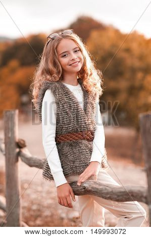 Beautiful blonde teenage girl 13-14 year old wearing fur vest white knitted sweater and beige pants. Posing at country side. Looking at camera. Autumn season.