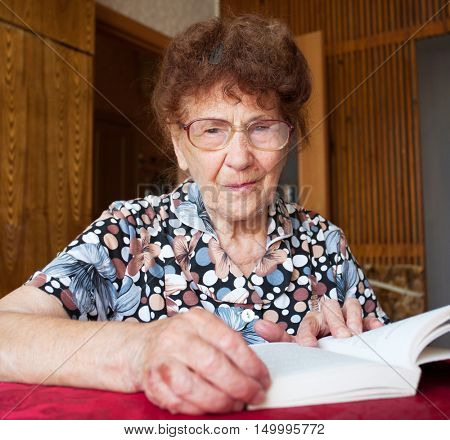 Old woman reading book. Elderly female at home