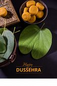 greeting card saying happy vijayadashmi or happy dussehra, indian festival dussehra, showing apta leaf or Bauhinia racemosa with traditional indian sweets pedha in silver bowl poster