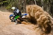 Motocross rider creates a large cloud of dust and debris poster