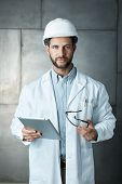 Portrait of confident young engineer wearing protective hardhat using ipad tablet. poster
