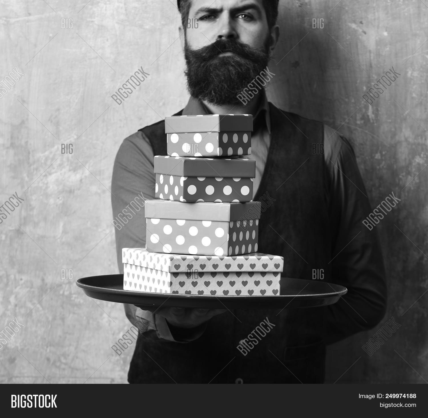 Waiter With Pink And Red Presents On Tray Businessman Serious Face Brings Gifts For Christmas Or Birthday Man Beard Holds Boxes Beige Wall