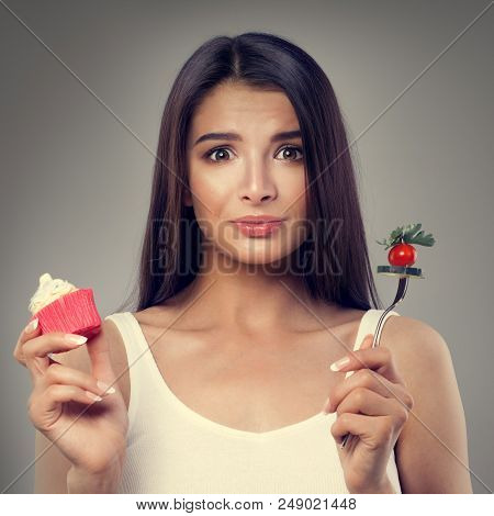 Unhappy Woman With Healthy And Unhealthy Food. Overweight, Healthy Eating And Diet Concept