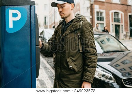 A Person Or A Tourist Pays For Car Parking In A Street Parking Machine.
