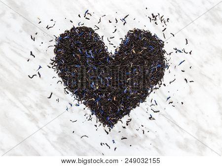 Heart Made Of Black Earl Gray Tea Leaves, On Marble Background. Tea Love.