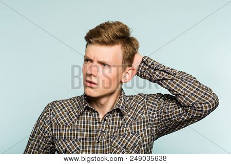 perplexed baffled confused man scratching head and looking owlishly at smth. portrait of guy on light background. emotion facial expression. feelings and people reaction concept. poster
