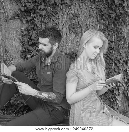 Couple In Love Sit Back To Back Outdoor, Nature Background. Couple With Busy Faces Reading Poems. Ro