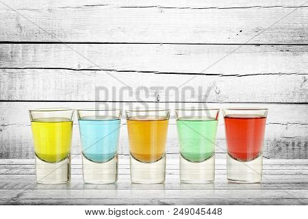 Close Up Of Five Colorful Shots On Weathered Wood
