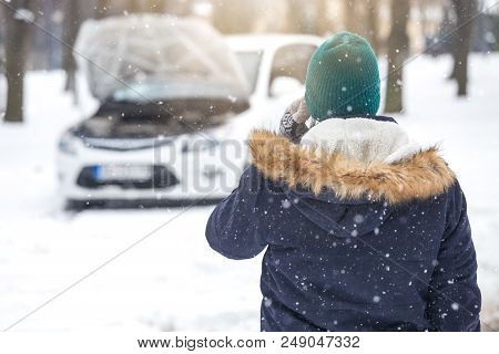 Rear View Of Man Using Smartphone And Calling For Help Because His Car Is Broken. Winter On The Road