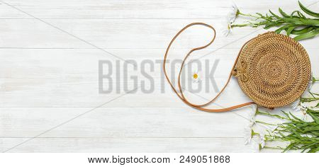 Fashionable Handmade Natural Organic Rattan Bag And Chamomile Flowers On Light Wooden Background. La