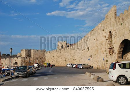 RHODES, GREECE - JUNE 12, 2018: The medieval fortified wall by Kolona harbour in Rhodes Old Town on the Greek island of Rhodes. The town is a UNESCO World Heritage Site.