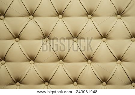 Coach-type leatherette screed tightened with buttons. Natural chesterfield style quilted upholstery backdrop close up. background texture poster