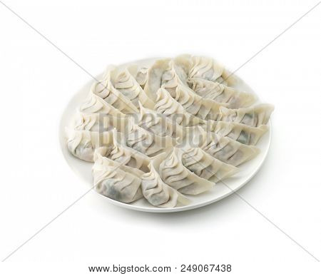 Raw Jiaozi dumplings wrapped in round flour skins, ready for cooking. Making Asian dumplings. Shallow depth of field.