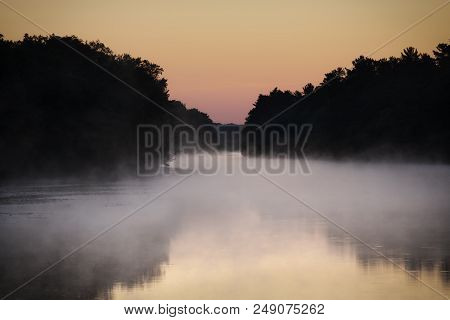 Soft Mist Hovering Over River Winding Through Wilderness, Sky And Water Lit By Sunrise Colors. Peace