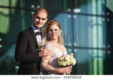 Tender Fiance And Fiancee On Their Wedding Day Standing Near Futuristic Modern Building With Big Win