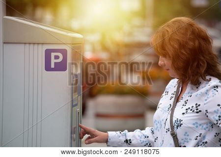 Woman using parking meter in parking zone area in a city