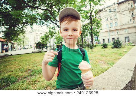 Cute Kid Boy Eating Ice Cream Outdoors. Urban Boy Enjoying Ice-cream In Summer Day. Smiling Happy Ki
