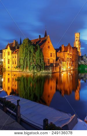 Scenic cityscape with a medieval fairytale town and tower Belfort from the quay Rosary, Rozenhoedkaai, at night in Bruges, Belgium poster