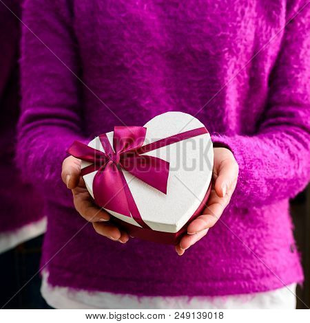 Unidentified Woman Holding A Small Gift. Concept Of Celebration Holidays And Surprise