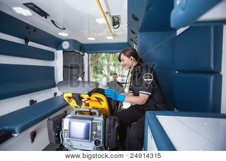 EMT worker listening to heart rate of patient
