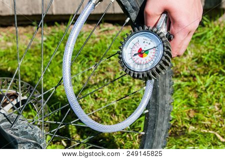 Person Inflating The Bicycle Wheel Whit The Air Compressor, Focus On The Manometer.