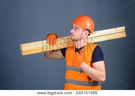 Wooden Materials Concept. Carpenter, Woodworker, Strong Builder On Serious Face Carries Wooden Beam