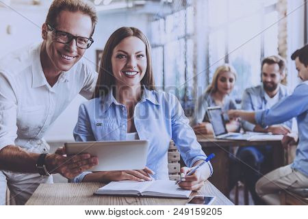 Handsome Businessman And Lady In Smart Casual Wear Looking At Camera And Smiling. Background Busines