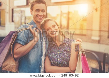 Beautiful Young Romantic Couple Keeping Shopbags. Man And Woman Looking At Camera And Smiling While