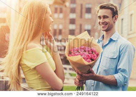 Handsome Young Man Gives Flowers To Cute Girl.. Beautiful Romantic Couple. Bouquet Of Pink Roses. Wo