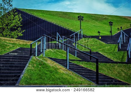 Katowice/poland- May 2, 2018: View Of Green Grass Lawns And Symmetric Black Stairs Near Internationa