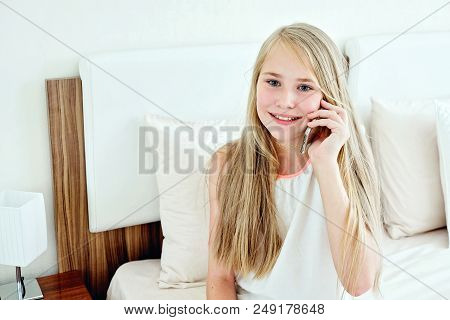 Teenage Girl Lying On Bed Using A Mobile Phone At Home