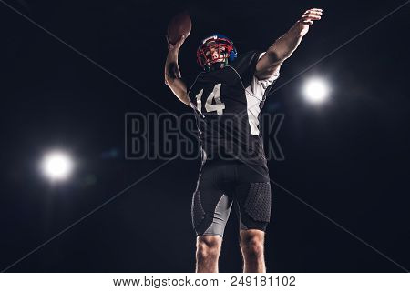 Bottom View Of American Football Player Throwing Ball Under Spotlights On Black