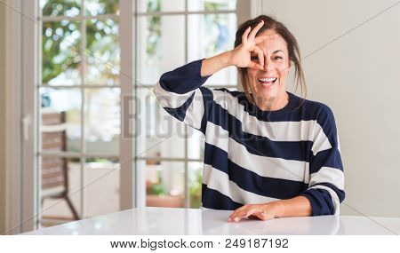 Middle aged woman with happy face smiling doing ok sign with hand on eye looking through fingers