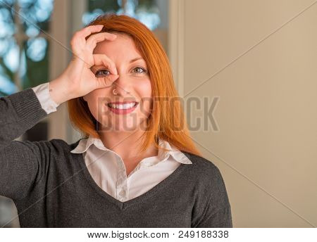 Redhead woman at home with happy face smiling doing ok sign with hand on eye looking through fingers