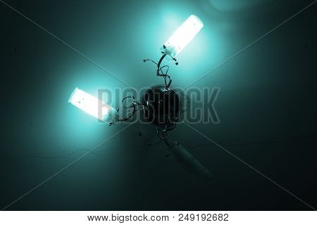 Modern Chandelier On Ceiling With Long Crack. Image In Hard Cyan Tint For Uniformity Of Illumination