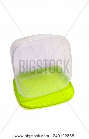 Transparent Plastic Container For Lunch, Lies On Its Green Flexible Lid. Isolated On White Backgroun