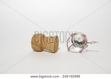 Wooden Cork And Muselet Of Expensive Sparkling Wine. Bottoms Of The Items And Pink Wire