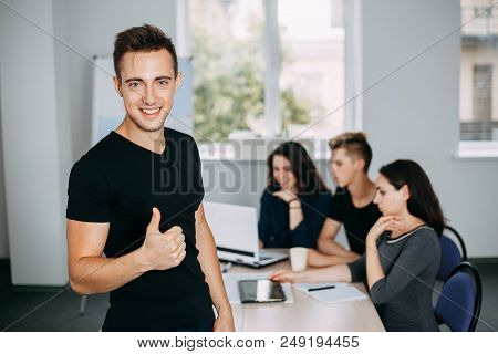Cheerful confident young man gesturing thumb up with his colleagues working behind him. friendly atmosphere, cohesive team, communication and comradery. poster