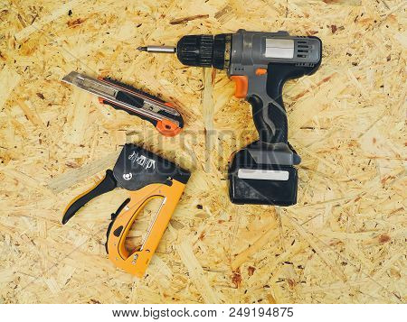 Drill, Construction Knife And Construction Stapler On A Wooden Background