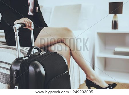 Cute Businesswoman With Suitcase Sitting On Bed. Beautiful Legs In High Heels. Important Business Tr