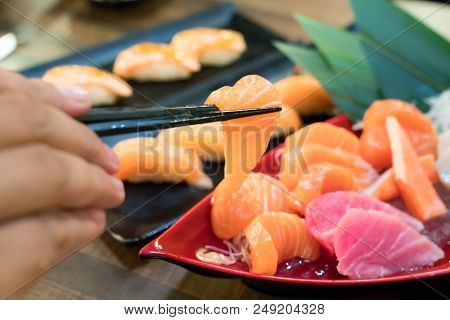 Chopsticks With Salmon Sashimi With Mixed Sliced Fish Sashimi On Ice In Black Bowl. Japanese Food In